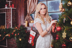 Woman near a new-year tree with gifts and candles Royalty Free Stock Photography