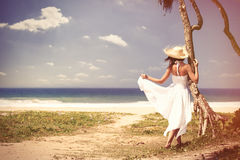 Woman near the ocean. Young woman in hat and white dress near the ocean. Back view Stock Image