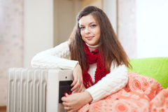 Woman near oil heater Stock Images