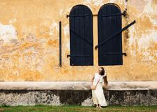 Woman near an old building. Woman near an old house with wooden shutters Stock Photography
