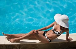 Woman near of pool. Young woman sitting on the ledge of the pool Stock Images