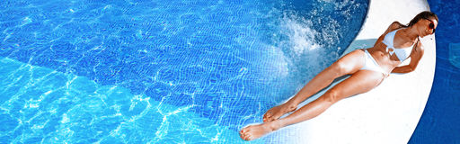 Woman near the pool. Beautiful woman relaxing near swimming pool. Vacation resort Stock Photo