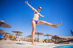 Woman near the pool, doing jumping up Stock Images