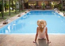 Woman near the pool. Woman in luxury spa resort near the swimming pool royalty free stock image