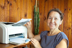 Woman near the printer pulls paper royalty free stock image