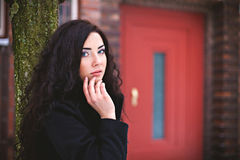 Woman near red entrance door at street Royalty Free Stock Images