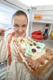 Woman near refrigerator. Happy woman eating sweet cake near refrigerator looking at camera Royalty Free Stock Images