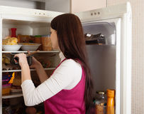 Woman  near refrigerator  at home Stock Photography
