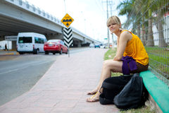 Woman near a road. Young woman sitting near a busy road, waiting for a bus Royalty Free Stock Image