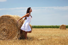 Woman near a rolled haystack. Gorgeous young woman standing near a rolled haystack and leaning on it Stock Photos
