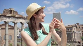 Woman near Roman forum using mobile in slow motion. Female tourist having video chat via online app stock footage