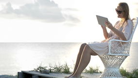 Woman near the sea watching photos using pad. Young woman sitting on the chair by the sea and watching pictures with tablet computer stock footage