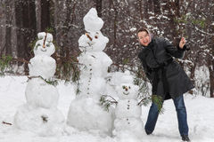 Woman near snowmen Stock Photos