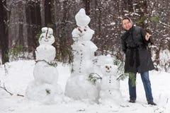 Woman near snowmen Stock Photography