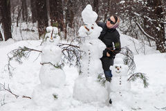 Woman near snowmen Royalty Free Stock Photo