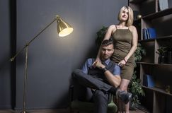 Woman near with successful rich man. Young successful businessman in chair and his woman in dress in luxurious apartment stock photos