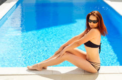 Woman near the sunlit pool Stock Photography