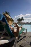 Woman near swimming pool in cuba. Woman wtih hat laying on deckchair over swimming-pool Stock Photo