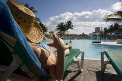 Woman near swimming pool in cuba. Woman wtih hat laying on deckchair over swimming-pool Stock Photography