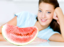 Woman near to a red water-melon Stock Photography