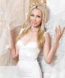 Woman near to a wedding dress dreams of wedding Stock Photos