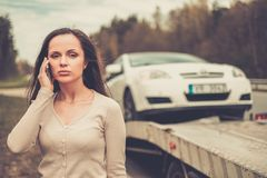 Woman near  tow truck picking up car Stock Photos
