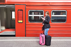 Woman near train checks his ticket on station Stock Photo