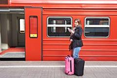 Woman near train checks his ticket on station Stock Photo