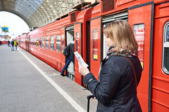 Woman near train checks his ticket on station Stock Photography