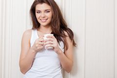 Woman near wall holding mug Stock Image