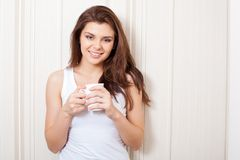 Woman near wall holding mug Stock Images