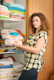 Woman near wardrobe with bed linen. Young woman near sliding-door wardrobe with bed linen Stock Photo