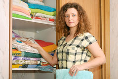 Woman near wardrobe with bed linen. Young woman near sliding-door wardrobe with bed linen Royalty Free Stock Images