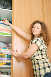 Woman near wardrobe with bed linen Stock Photo