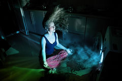 Woman near by washing machine underwater. Frustrated woman in meditation pose near by washing machine glowing inside underwater stock image