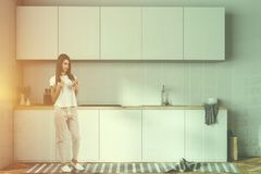 White kitchen countertops and closets, woman. Woman near white kitchen counters with a cooker, kitchenware and bottles on them. A row of closets hanging above it stock image