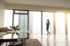 Woman near the window. Full length view of happy young woman model standing near the window with a cup of coffee in luxury modern apartment, looking at cityscape Stock Image