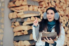 Excited Girl Pointing Her Finger Up and Holding Some Firewood. Woman near woodpile having an idea about cost effective heating royalty free stock photography