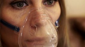 Woman in nebulizer mask making inhalation for asthma treatment stock footage