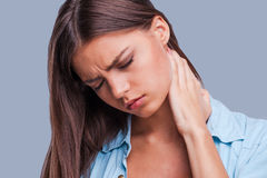 Woman with neck pain. Young woman holding her aching neck standing against grey background Royalty Free Stock Images