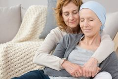 Woman comforting friend with cancer. Woman with a necklace comforting her friend with cancer, both of them have their eyes closed Royalty Free Stock Image