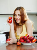 Woman with nectarines in  kitchen Stock Photos