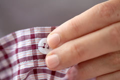 Woman with needle stitching on button to shirt Stock Photos
