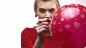 A woman with a needle is threatening to burst the balloon, slow motion. Young woman is holding a balloon and a needle and threatening to burst the balloon stock video footage