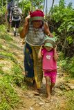 A woman of Nepal and her young son carry a sack tied to their forehead by a strap.