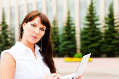 Woman with netbook. Business woman working on the street with netbook Royalty Free Stock Photography