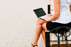 Woman with netbook. Business woman sitting on a bench with a netbook Royalty Free Stock Photos