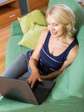 Woman with netbook sitting on sofa Royalty Free Stock Image