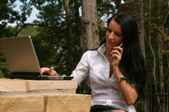 Woman networking. Young woman using a laptop and cell phone to network Stock Images