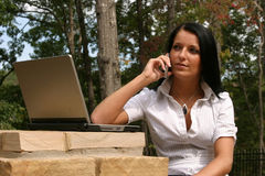 Woman networking. Young woman using a laptop and cell phone to network Stock Image
